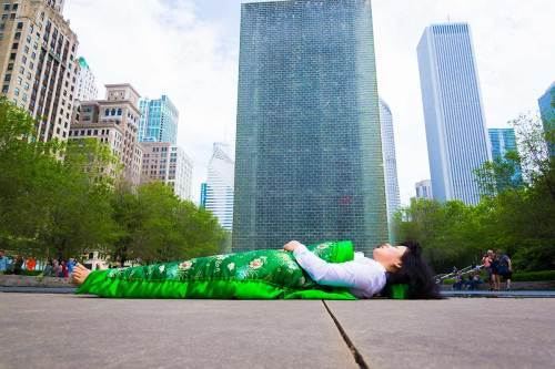 each time Chun Hua Catherine Dong travels to a city, she takes photographs of herself lying in front of historical and tourist sites, covered by a silk corpse duvet