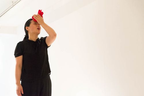 Chun Hua Catherine Dong's performance in New York: she wrapped rice with red handkerchiefs, press the rice ball on her forehead and call her name to come home three times with her 	Chinese dialect